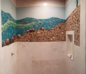 custom mosaic inlaid in marble of a underwater beach scene with the sky above made of different size glass gems and pebble surround encased in clear epoxy